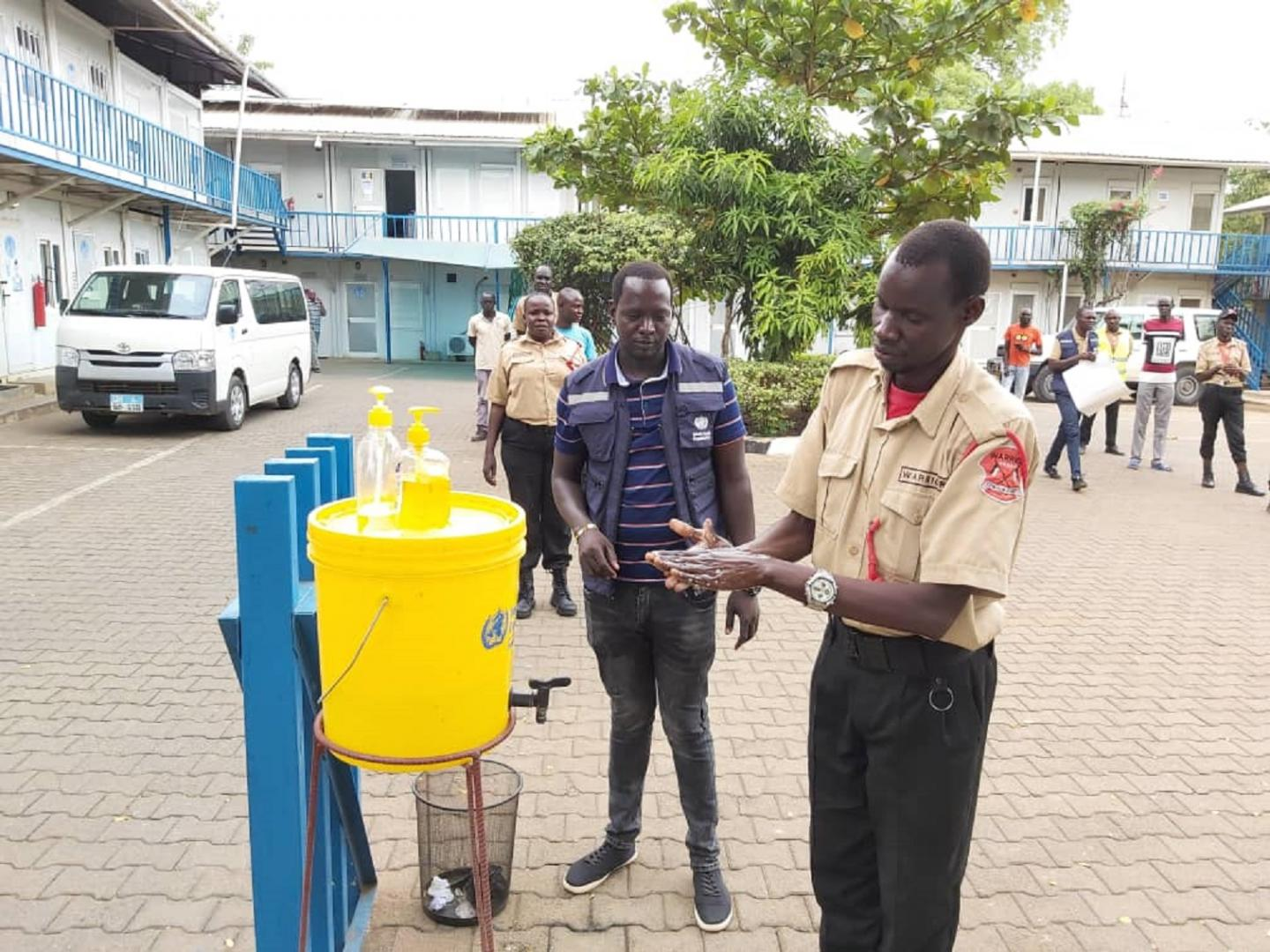 southsudan_covid-19_Security_guards_deployed_at_WHO_office_in_Juba_practices_hand_washing_as_a_recommended_measure_to_prevent_the_spread_of_COVID-19.jpg